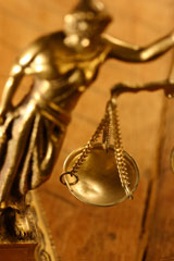 A golden scale hangs in from blindfolded Justice